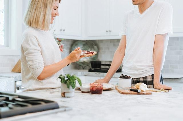 Muž a žena v kuchyni u snídaně, stojí u linky a mají připravené jídlo