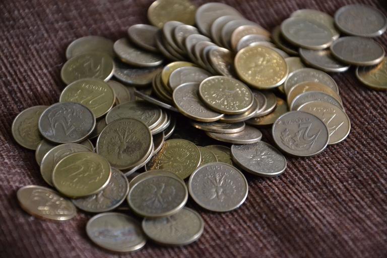 Mince rozsypané na stole, na tmavším ubrusu.