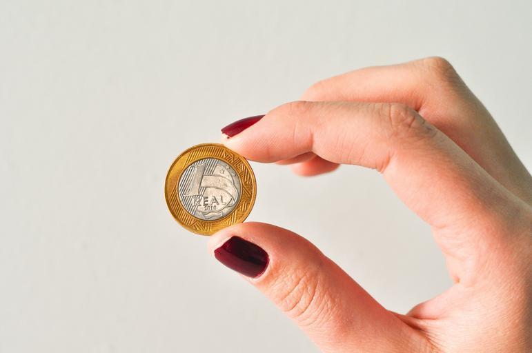 ruka drží jednu minci pomocí nalakovaných nehtů vínovou barvou