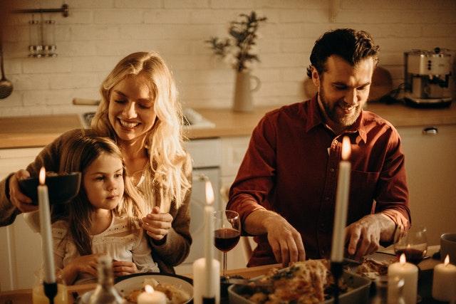 rodina u stolu jí, plný stůl jídla, svíčky zapálené, muž krájí, žena má na klíně holčičku