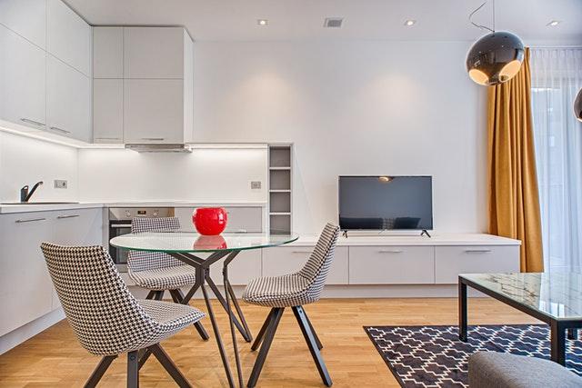 kuchyně, kuchyňská linka bílá, vedle stůl a kárované černobílé židle, a stolek s televizí