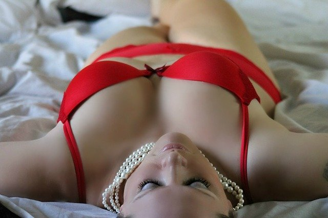 woman in red underwear lying on a bed